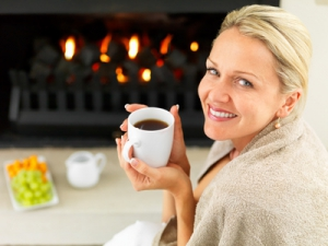 Portrait of a mature woman by the fireplace having a hot cup of coffee